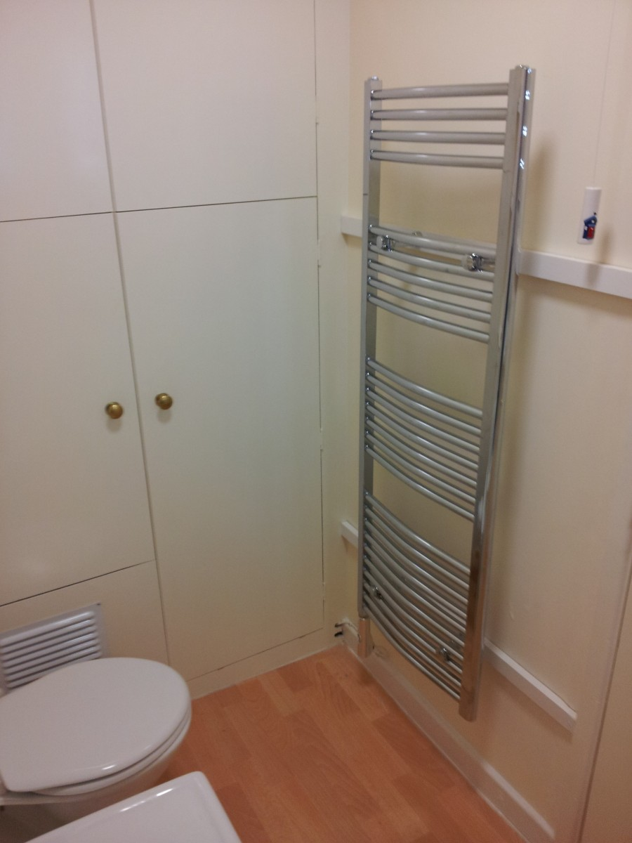 The bathroom has a bath, shower and towel rail for drying your towels.